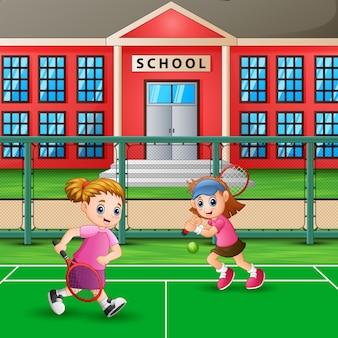 学校のコートでテニスをする女の子たち