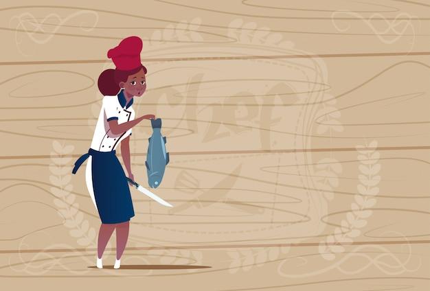 Женщина афроамериканец шеф-повар держит рыбу мультфильм шеф-повар в форме ресторана на деревянном текстурированном фоне
