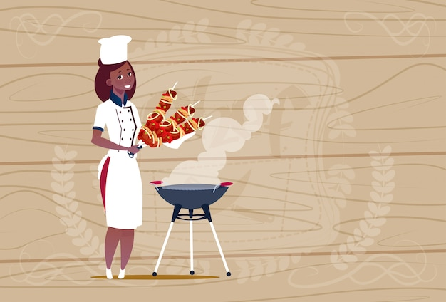 Female african american chef cook holding kebab cartoon chief in restaurant uniform over wooden textured background