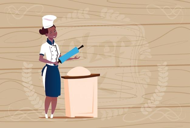 Женщина афроамериканец шеф-повар работает с тестом мультфильм начальник в форме ресторана на деревянный текстурированный фон