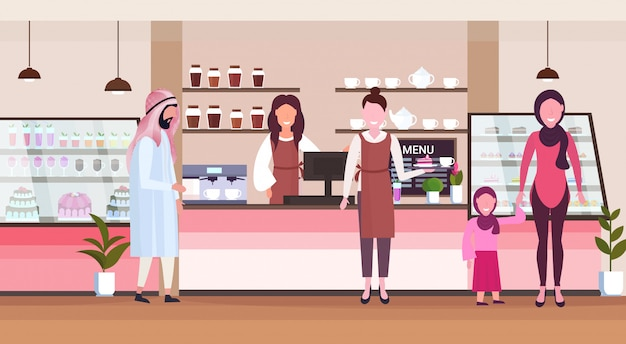 Female barista coffee shop worker serving arab people clients giving glass of hot drink waitress standing at cafe counter modern cafeteria interior flat full length horizontal