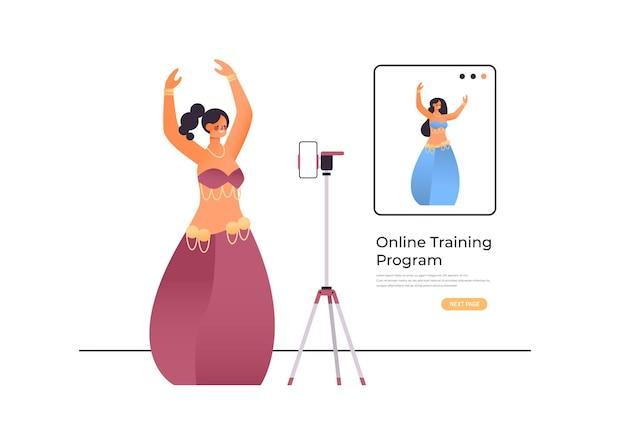 동부 스타일의 옷을 입은 여성 댄서는 온라인 비디오 교육 프로그램 운동 개념을 연습합니다.