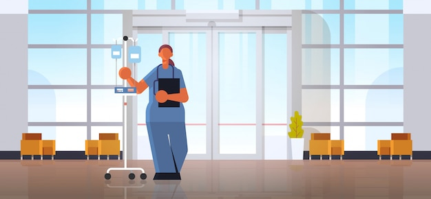 Female doctor anesthesiologist in uniform holding dropper medicine healthcare concept modern hospital medical clinic hall interior full length horizontal flat