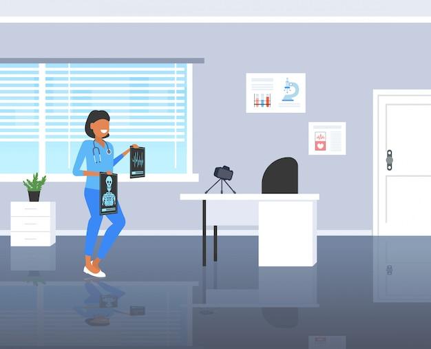 여성 의사 블로거 삼각대 의학 블로그 개념 현대 클리닉 인테리어 전체 길이 가로에 카메라로 x 선 사진 외과 의사 녹화 비디오를 검사