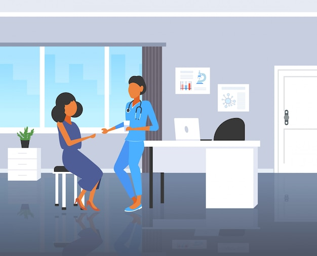 Female doctor giving pill and glass of water to woman patient pharmacist offering pills medication healthcare concept modern hospital room interior full length