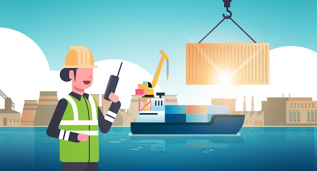 Female engineer using walkie-talkie controlling crane hook lifting cargo container box