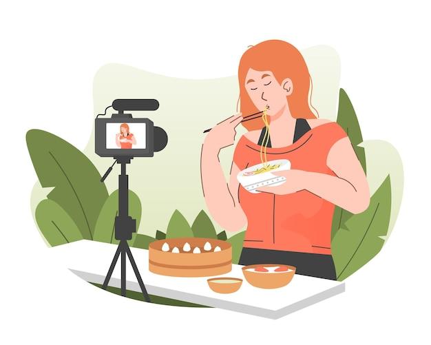 그녀의 온라인 비디오 채널에 비디오를 녹화하면서 국수를 먹는 여성 음식 블로거