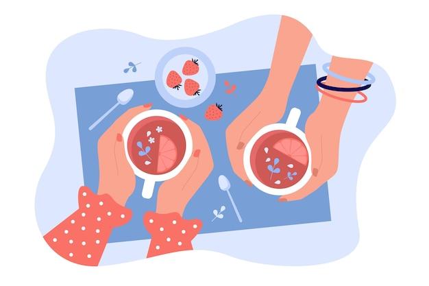 Подружки пьют травяной ягодный чай. вид сверху на чашки или кружки в человеческих руках. встреча людей в кафе