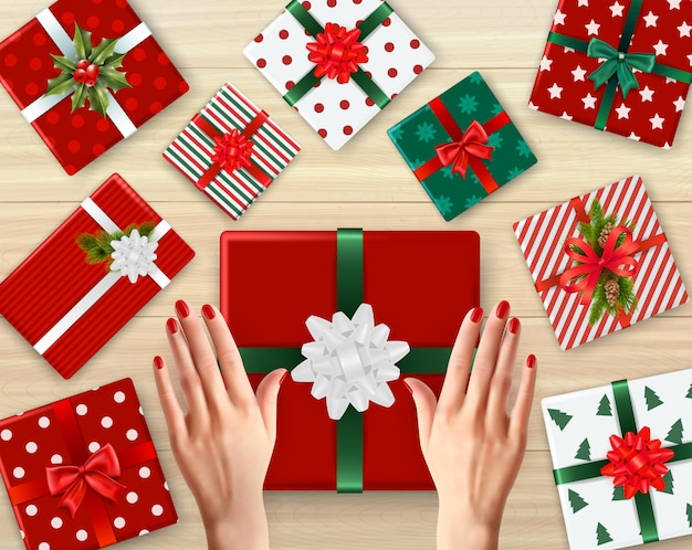 Female hands and decorated cardboard gift boxes of different color realistic background