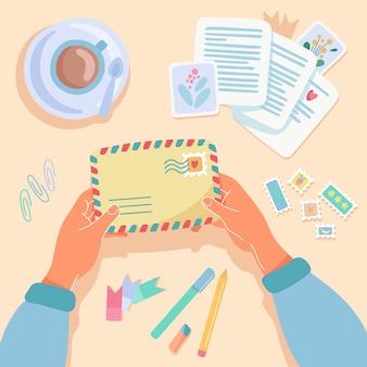 Женские руки, держа бумажный конверт. почтовые марки, открытки, ручки, макет чашки кофе на столе. вид сверху. пост пересечение, отправка бумажных писем концепции. плоский мультфильм иллюстрации