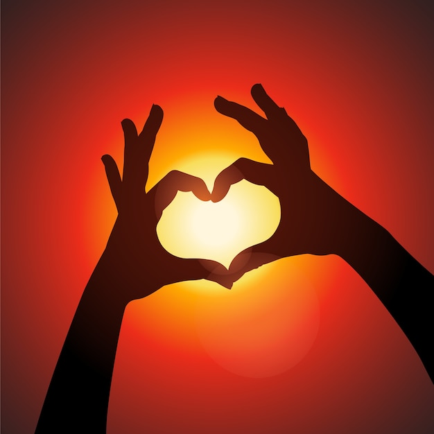 日没の背景に指でサインハートを作る女性の手バレンタインデーの愛の概念