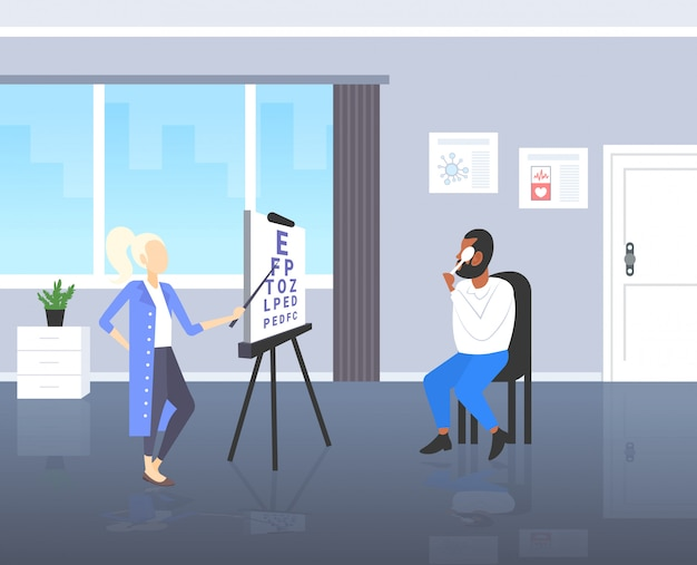 Female ophthalmologist checking eye vision of african american man patient eyesight doctor in uniform pointing letters at chart medicine healthcare concept modern clinic room interior full length