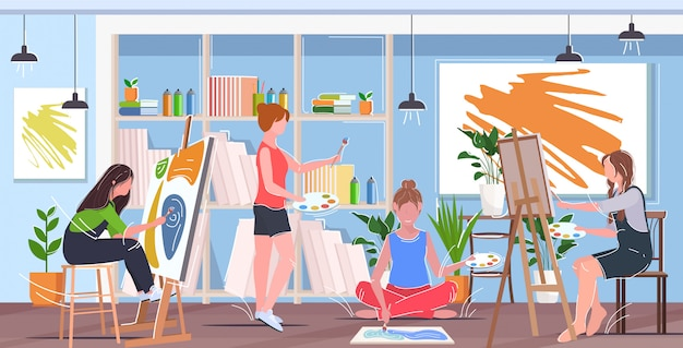 Female painters using paintbrush and palette mix race women artists drawing pictures concept modern art studio interior horizontal