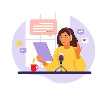 Женский подкастер разговаривает с микрофоном, записывая подкаст в студии. радиоведущий со столиком