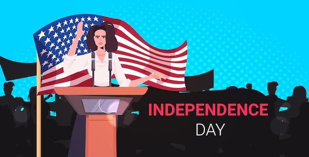 トリビューンからの人々に話す女性政治家、7月のアメリカ独立記念日のお祝いのバナーの4日
