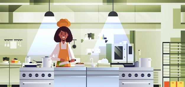 Female professional chef cook chopping vegetables on carving board african american woman in uniform preparing salad cooking food concept modern restaurant kitchen interior portrait