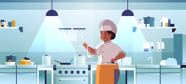 Female professional chef cook preparing and tasting dishes african american woman in uniform near stove cooking food concept modern restaurant kitchen interior portrait