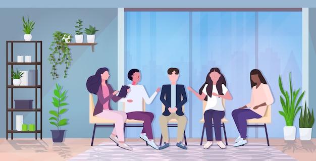 Женщина-психолог разговаривает с группой пациентов во время сеанса психотерапии, лечение стрессовой зависимости и психических проблем