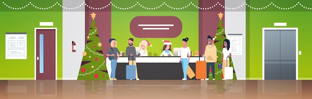 Female receptionists in santa hats meeting  tourists with luggage at reception counter registration christmas holiday concept modern hotel lobby interior