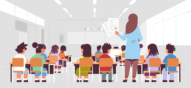 Female teacher holding tests with good a grade rear view pupils group sitting in classroom during lesson teaching education concept modern class room interior