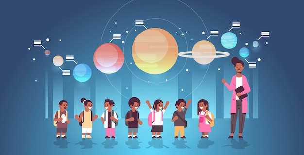 Female teacher with african american schoolchildren in observatory solar system exploration school trip excursion to planetarium astronomy lesson concept flat full length horizontal