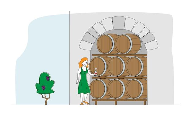 Женский винодел, дегустирующий вино в винном погребе с дубовыми бочками.