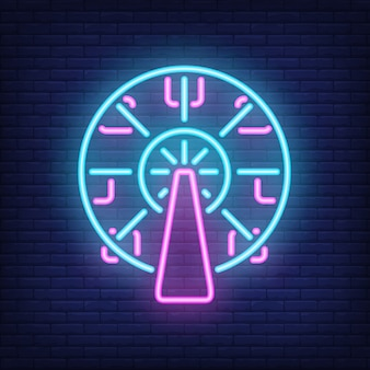 Ferris wheel neon sign. amusement park carousel on dark brick wall background.