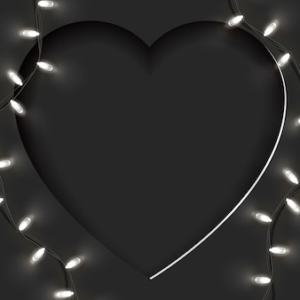 Festive card of large paper cut heart shape and bright garland with empty space for your copy. suitable for valentine's day, woman's day, mother's on black  .