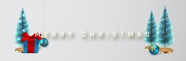 お祝いのクリスマスの背景。赤いリボン、松の木、光沢のあるキラキラ光るクリスマスボールが付いたクリスマスギフトボックス。