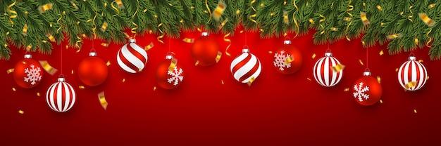 紙吹雪とクリスマスの赤いボールとモミの木の枝とお祝いのクリスマスバナー。