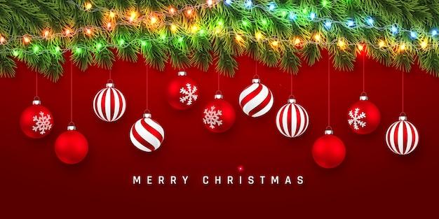 Праздничный фон рождество или новый год. рождественские еловые ветки с легкой гирляндой и рождественскими красными шарами. фон праздника.