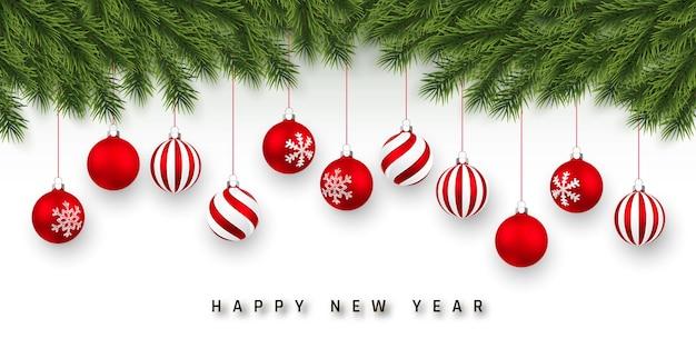 お祝いのクリスマスや新年の背景。クリスマスツリーの枝とクリスマスの赤いボール。