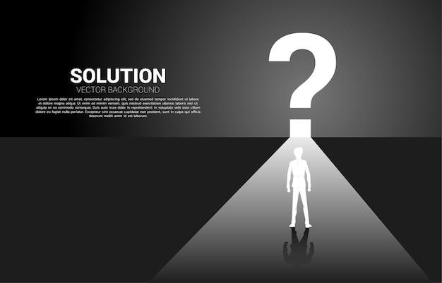 Найдите концепцию решения. силуэт бизнесмена, бегущего к значку вопросительного знака с освещением