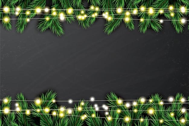 Еловая ветка с неоновыми огнями на фоне классной доски