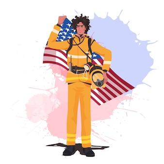 アメリカの旗の幸せな労働者の日を保持している制服を着た消防士