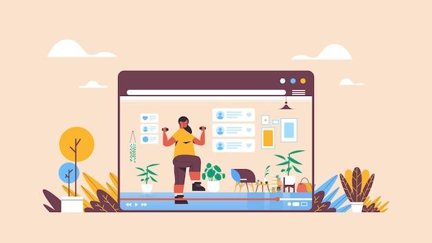 オンラインビデオブログライブストリーミングブログコンセプトガールvloggerをウェブブラウザーウィンドウの水平方向に記録するダンベルでエクササイズを行うフィットネスブロガー