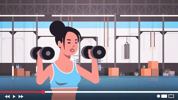Фитнес-блогер делает упражнения с гантелями спортсменка