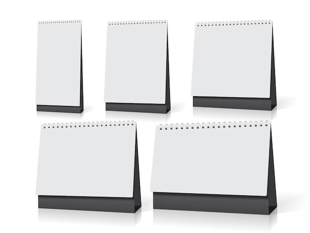 Стоят пять белых пустых настольных календарей разных размеров