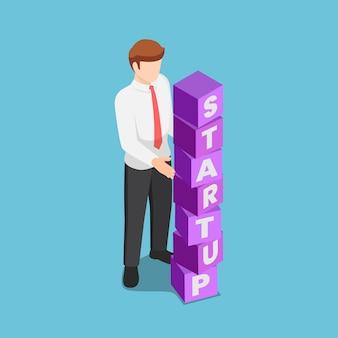 Startupという言葉でブロックを配置するフラットな3dアイソメトリックビジネスマン。起業のコンセプト。