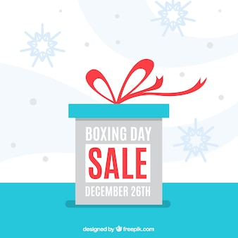 Flat boxing day background with gift and snowflakes