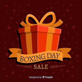 Flat boxing day sale with wrapped gift box and ribbon Premium Vector