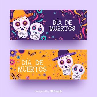 Flat día de muertos skulls with sombrero banners