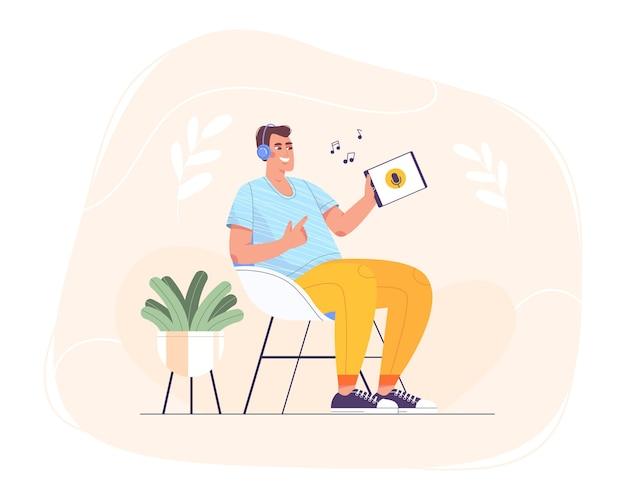 헤드폰을 끼고 의자에 앉아 온라인 자기 교육을 위해 태블릿을 사용하는 평평한 행복한 십대. 웃고 있는 남자는 장치에서 음악, 라디오, 강의, 팟캐스트 또는 디지털 오디오북을 들으며 휴식을 취합니다.