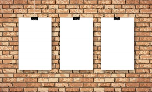 茶色のレンガの壁に3つの空の白いポスターとフラットインテリア。トレンディなロフトルームの風景の背景、ファッションギャラリー展覧会のインテリア。