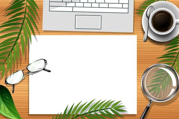 緑の葉とオフィス要素を持つオフィスワークデスクのフラットレイ