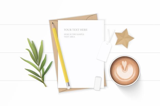 Плоский вид сверху элегантный белый состав письмо крафт-бумага конверт кофе карандаш звезда ремесло тег лист эстрагона и ластик на деревянном фоне.