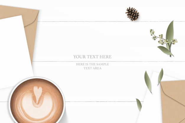 Flat lay top view elegant white composition letter kraft paper envelope pine cone leaf flower and coffee on wooden background.