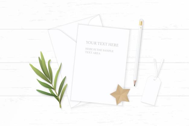 Плоский вид сверху элегантный белый состав письмо бумажный конверт карандаш тег звездное ремесло и лист эстрагона на деревянном фоне.