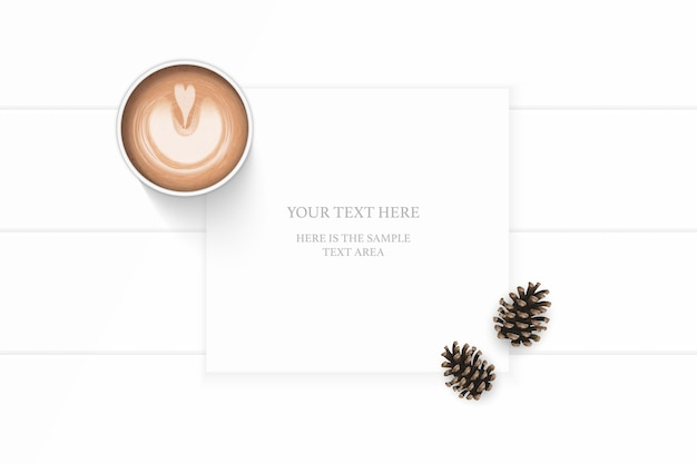 Flat lay top view elegant white composition paper brown pine cone and coffee on wooden background.