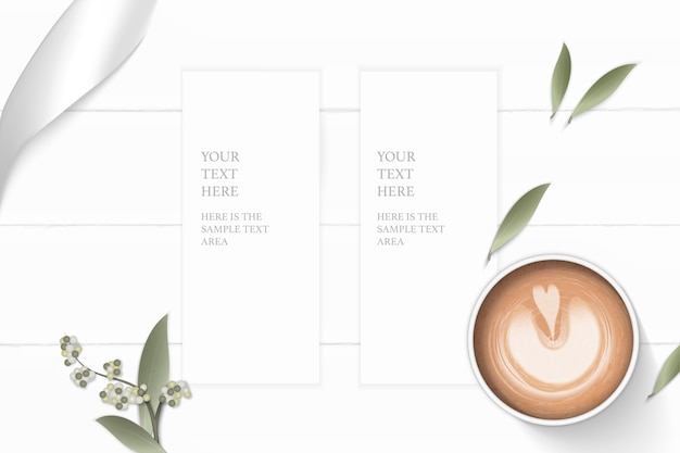 Flat lay top view elegant white composition paper flower leaf coffee and silver ribbon on wooden background.